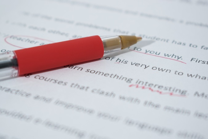 editing and proofreading services; picture of paper and red pen with markings