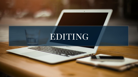editing title graphic, laptop, notebook, pen, and water glass in background. Editing services